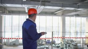Vorarbeiter in einer Fabrik in einem Schutzhelm Zeitlupe stock video footage