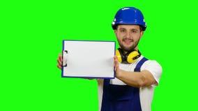 Vorarbeiter hebt das Papier-planchette auf und lächelt Grüner Bildschirm stock video footage
