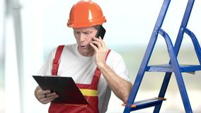 Vorarbeiter mit Klemmbrett und Telefon stock footage
