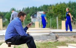 Vorarbeiter oder Ingenieur, die eine Textnachricht lesen Lizenzfreies Stockbild