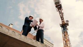 Vorarbeiter sprechen über Bauplan stock video footage