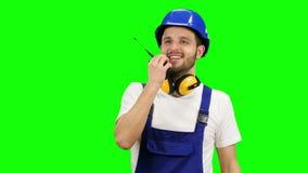 Vorarbeiter spricht in einem Funksprechgerät mit den Kollegen Grüner Bildschirm stock video
