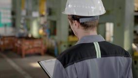 Vorarbeiter trägt Schutzhelm und geht in eine Werkstatt während des Arbeitstages, Überwachungsarbeiter stock video footage
