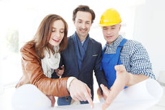 Vorarbeiter zeigt Hauspläne zu den Paaren Stockbilder