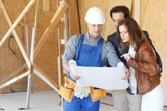Vorarbeiter zeigt Hauspläne zu den Paaren Lizenzfreie Stockfotos