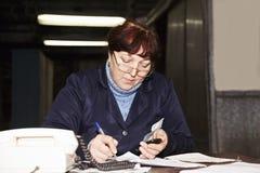 Vorarbeiterinschreiben am Schreibtisch lizenzfreie stockbilder
