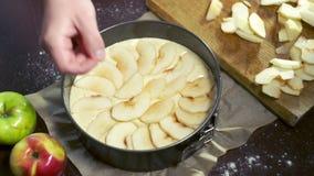 Vorbereiten für backenden Apfelkuchen Koch setzt Apfelscheiben in Backform ein stock video footage