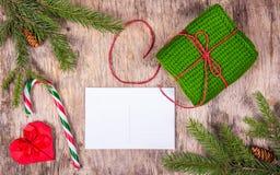 Vorbereiten für Weihnachten Leere Postkarte, Ingwerkeks und gestricktes Geschenk auf altem hölzernem Brett Kopieren Sie Platz stockfotografie