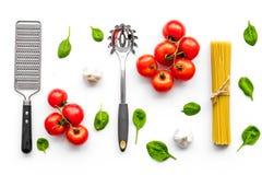 Vorbereiten, Teigwaren zu kochen Spaghettis, Tomaten, Knoblauch, Käsereibe, Löffel für Spaghettis auf Draufsicht des weißen Hinte stockfoto
