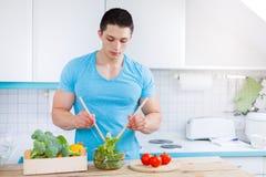 Vorbereiten von gesunder Ernährung c des jungen Mannes des Salatlebensmittelmittagessengemüses lizenzfreie stockbilder