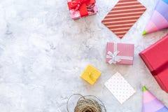 Vorbereiten zur Feier Farbige Geschenkboxen und Parteihüte auf grauem Steincopyspace Draufsicht des hintergrundes Lizenzfreie Stockfotografie