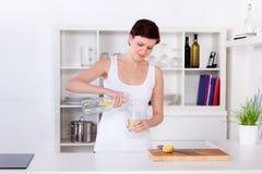 Vorbereitende und trinkende Limonade der jungen Frau in ihrer Küche lizenzfreie stockfotos