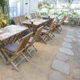 Vorbereitete Holztische und Stühle mit Blumendekorationen und gepflasterter Steinboden im Innengartenrestaurant stockbild
