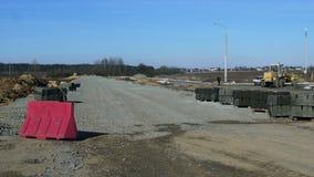 Vorbereiteter Platz für Straßenbau, Blöcke von Beschränkungen sind auf dem Straßenrand stock footage