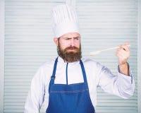 Vorbereitung der Nahrung Gesundes Lebensmittelkochen B?rtiger Mannkoch in der K?che, kulinarisch Chefmann im Hut Geheimes Geschma stockfotografie