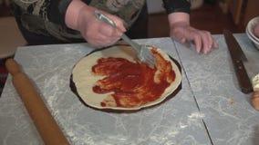 Vorbereitung der selbst gemachten Pizza auf einem hellen Küchentisch, Nahaufnahmeschuß stock video footage