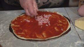 Vorbereitung der selbst gemachten Pizza auf einem hellen Küchentisch, Nahaufnahmeschuß stock video