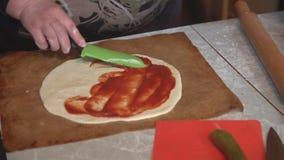 Vorbereitung der selbst gemachten Pizza auf einem hellen Küchentisch, Nahaufnahmeschuß stock footage