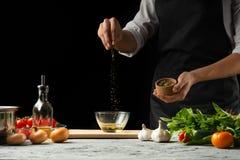 Vorbereitung der Tomatensauce durch die Hände des Chefs, Schritte der Prozess in der Küche auf einer schwarzen Hintergrundkopie d lizenzfreies stockfoto