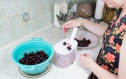 Vorbereitung des Kuchens mit Kirschen und Himbeeren. Stockbilder