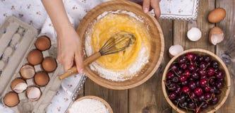 Vorbereitung des selbst gemachten süßen Gebäcks mit Kirschen Eier, Mehl und Beeren auf einem hölzernen Hintergrund Hände im Rahme stockfotos