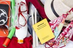 Vorbereitung für Feiertag, Gepäck mit Badebekleidung, Tuch, Sonnenbrille, suncream, Flipflops, Strohhut, Schutzimpfungsdurchlauf stockbilder