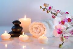 Vorbereitung für Massage im Weiß mit Tüchern, Steinen, Kerzen und Orchidee Stockfotografie