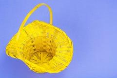 Vorbereitung für Ostern Gelber Korb mit Hühnereien auf violettem Hintergrund Lizenzfreie Stockfotos