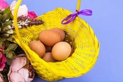 Vorbereitung für Ostern Gelber Korb mit Hühnereien auf violettem Hintergrund Lizenzfreie Stockbilder