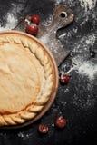 Vorbereitung für Pizza, Mehl und Tomaten auf einem runden hölzernen Brett auf einem schwarzen Holztisch Stockfoto