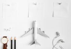 Vorbereitung für reisendes Konzept, Uhr, Flugzeug, Bleistifte, Papierbekanntes, Kopfhörer, Stoßstift Lizenzfreie Stockbilder