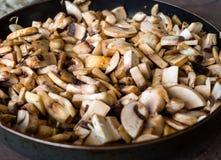 Vorbereitung von gebratenen Pilzen und von Zwiebel in einer Bratpfanne Lizenzfreies Stockbild