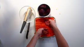 Vorbereitung von Heringen unter einem Pelzmantel Der Mann verteilt die gekochten Karotten gleichmäßig über die Schicht von Kartof stock video footage