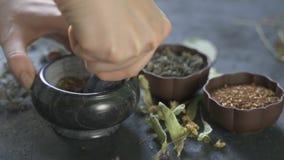 Vorbereitung von medizinischen Kräutern für Gebrauch Heilpflanzen auf dem Tisch Frau reibt Heilpflanzen in einem Mörser stock video