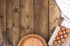 Vorbereitung von selbst gemachten Kuchen auf einem hölzernen Hintergrund Bestandteile und Zubehör für die Küche und zu Hause Schü lizenzfreies stockbild