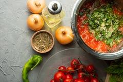 Vorbereitung von Tomatensaucen und Gewürzen Kirschtomaten, Gewürze, Paprikapfeffer Ansicht von oben auf einem grauen Hintergrund  lizenzfreie stockbilder