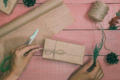 Vorbereitung von Weihnachtsgeschenken Geschenkboxen werden mit Kraftpapier verpackt Stockfoto
