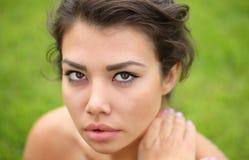 Vorbildliche Aufstellung der Frau gegen grünes natürliches Stockfotografie