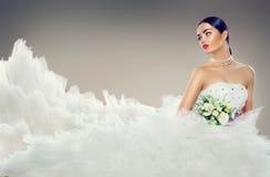 Vorbildliche Braut der Schönheit im Hochzeitskleid mit langem Zug