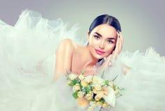 Vorbildliche Braut der Schönheit im Hochzeitskleid mit langem Zug Stockfotografie