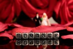 Vorbildliche Hochzeitspaare mit dem Wort Romance auf Perlen und rosafarbenem Blumenstrauß Lizenzfreie Stockfotos