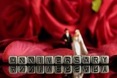 Vorbildliche Hochzeitspaare mit dem Wortjahrestag auf Perlen und rosafarbenem Blumenstrauß Stockfoto