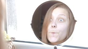 Vorbildliche Jugendliche der Schönheit, die im Spiegel schaut und lustige Gesichter macht 4K stock video