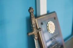 vorbildliche Klinge und Plakette des Mittelalters auf dem hölzernen Regal stockfotos