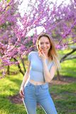 Vorbildliche Stellung des glücklichen blonden weiblichen Fotos im Park mit Blütenhintergrund Stockbild