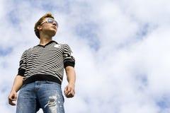 Vorbildliche Stellung des jungen schönen Mannes unter der Wolke Lizenzfreie Stockfotografie