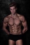Vorbildlicher sexy Mann in der Unterwäsche, schwarzer Schmutzhintergrund Stockfoto
