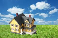 Vorbildliches Haus auf grünem Gras mit Himmel Stockfotografie