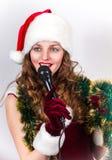 Vorbildliches Holdingkaraoke und tragender Weihnachtshut Lizenzfreie Stockfotografie