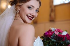 Vorbildliches lächeln der nahen Ansicht und seine schönen weißen Zähne vorführen Ein Blumenstrauß von roten Rosen kommt zum Kuche Stockfotografie
